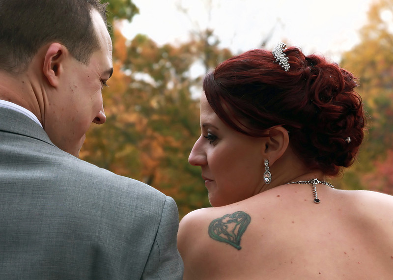 Groom and bride in front of fall leaves.