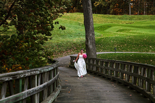 Photograph of bride in the distance on wood bridge in nature.