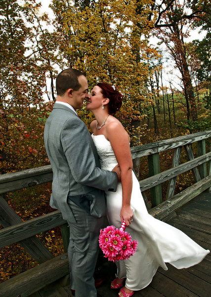 Bride and groom smiling and embracing on old wood bridge in fall foliage.