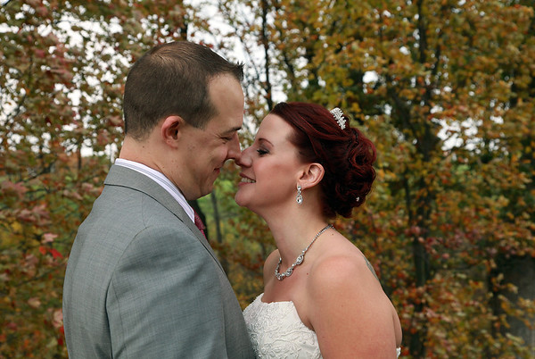 Groom and bride smiling at each other in front of golden autumn trees.